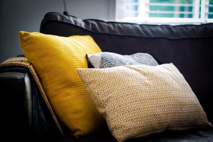 three assorted-color throw pillows on black sofa