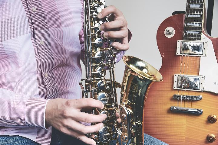 在吉他旁边演奏萨克斯的男人